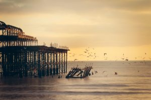 image of a pier with birds flying